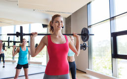 Group of women excercising with bars in gym Stock Image