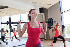 Group of women excercising with bars in gym Stock Photos