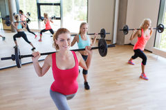 Group of women excercising with bars in gym Stock Images