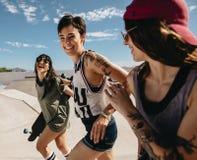 Women friends running outdoors at skate park. Group of women friends running outdoors at skate park. Female skaters enjoying at skate park Stock Photography