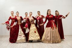 Group of women in gorgeous ball dresses view. Group of women in gorgeous red ball dresses full-length view stock photo