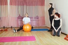Group of women in gym. One sitting on floor with ball stretching out legs, another looking at her smiling. Trainer looking to mirror. Horizontal shot Stock Photography