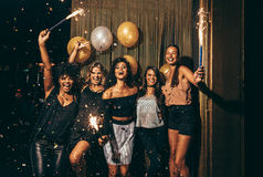 Group of women having party at nightclub. Shot best friends celebrating new year`s eve holding sparklers in a party. Group of women having party at nightclub Royalty Free Stock Image