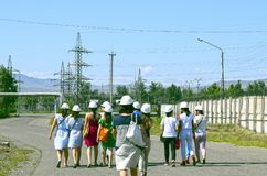 A group of women in helmets walking along the road to an industrial, power facility royalty free stock photos