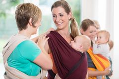 Group of women learning how to use baby slings for mother-child. Bonding royalty free stock images