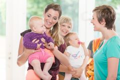 Group of women learning how to use baby slings for mother-child. Bonding stock images
