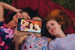 Group of women making selfie on smartphone, lay on grass during picnic Stock Photo