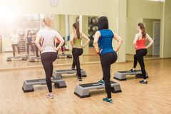 Group of women making step aerobics from the backside. Group of women making step aerobics in fitness club - view from the backside royalty free stock photos