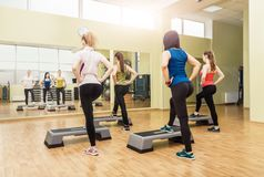 Group of women making step aerobics from the backside Stock Images