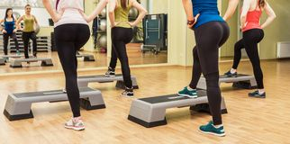 Group of women making step aerobics from the backside Royalty Free Stock Photo