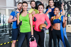 Group of women and men in gym posing at fitness training Stock Photos
