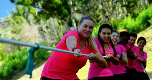 Group of women playing tug of war during obstacle course. In the boot camp stock video footage