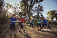 Group of women playing tug of war during obstacle course training. In the boot camp Royalty Free Stock Images