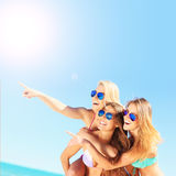 Group of women pointing at something on the beach Stock Photos