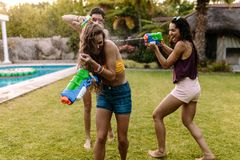 Happy friends doing water gun battle at poolside. Group of women at the poolside having water gun battle. Female friends playing with water guns royalty free stock photo