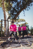 Group of women practicing tyres obstacle course. In the boot camp Royalty Free Stock Photography