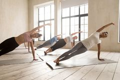 Group of women practicing yoga lesson doing Side Plank pose stock photos