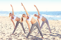 Group of women practising yoga on the beach Stock Photography