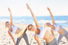 Group of women practising yoga on the beach Stock Photos