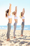 Group of women practising yoga on the beach Stock Image