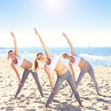 Group of women practising yoga on the beach Stock Photo