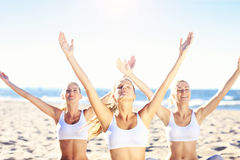 Group of women practising yoga on the beach Royalty Free Stock Photography