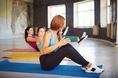 Group of women rest on mats between exercise sets Stock Image