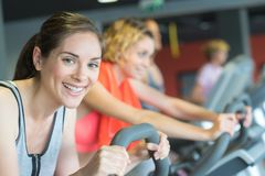 Group women riding on exercise bike in gym stock photography