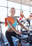 Group of women riding on exercise bike in gym Royalty Free Stock Image