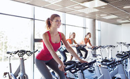 Group of women riding on exercise bike in gym Royalty Free Stock Photo