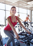 Group of women riding on exercise bike in gym Royalty Free Stock Photos