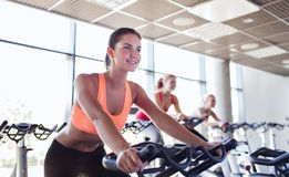 Group of women riding on exercise bike in gym Stock Photos