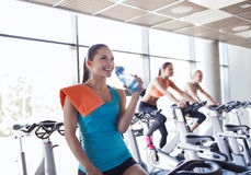 Group of women riding on exercise bike in gym. Sport, fitness, lifestyle, equipment and people concept - group of women with water bottle riding on exercise bike stock photo