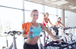 Group of women riding on exercise bike in gym Stock Image