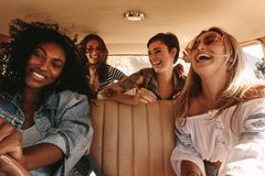 Group of women on road trip. Group of four women on a road trip. Multiracial female friends traveling by a car and enjoying stock photography