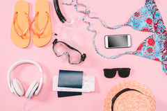 Group of women`s casual outfits with gadgets and snorkeling equipment on pink background Royalty Free Stock Photos