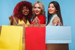 Group of women at shopping on Black Friday holiday. Beautiful young women make shopping in black friday holiday. Girls with bag on lgiht background royalty free stock photography