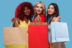 Group of women at shopping on Black Friday holiday. Beautiful young women make shopping in black friday holiday. Girls with bag on lgiht background Royalty Free Stock Images