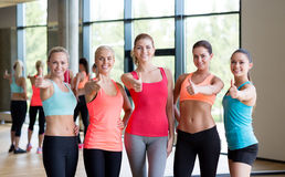 Group of women showing thumbs up gesture in gym Stock Images