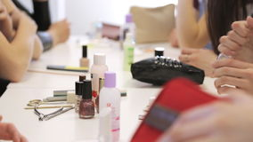 Group of women sits at table and practice in caring about their hands. Workplace is full of various tools, that are useful for manicure, such as nail lacquers stock video