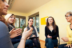 Group Of Women Sitting In A Circle, Discussing. A group of women are sitting in a circle, discussing Stock Photography