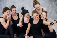 Group of women sitting and relaxing after a long yoga class and taking selfie Stock Image
