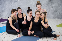 Group of women sitting and relaxing after a long yoga class and taking selfie stock photos