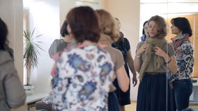 Group of women stands in front of the mirror talking to each other. One lady bends a beige scarf around a neck by making two loops around it and then secures a stock video