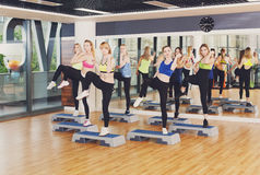 Group of women, step aerobics in fitness club. Group of young women in fitness class do step aerobics. Girls at step do leg kicks. Healthy lifestyle at gym Royalty Free Stock Photos