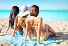 Group of women in swimwear sunbathing on beach Stock Photo