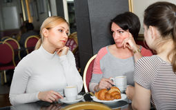 Group of women taking a complicated conversation. Group of ordinary tired angry women taking a complicated conversation over a cup of coffee royalty free stock image