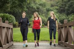 Group women in their 30s walking together in the outdoors. Stock Photo