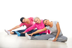 Group of women training. Group of three women training and stretching legs on floor over white background Royalty Free Stock Image
