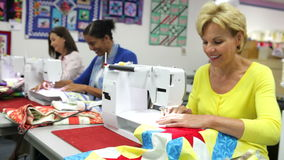 Group Of Women Using Electric Machines In Sewing Class Stock Photo